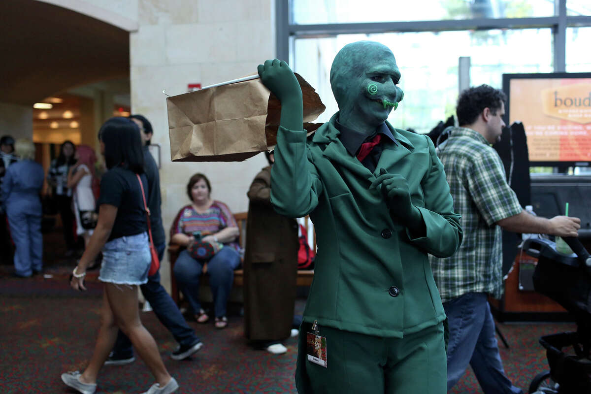 Brittany Hernandez, of Corpus Christi, who is dressed as Calliope from Homestuck, takes the bag off her head, also part of her costume, so participants can photograph her during San Japan Sinister 6 at the Henry B. Gonzalez Convention in San Antonio on Saturday, August 17 2013.