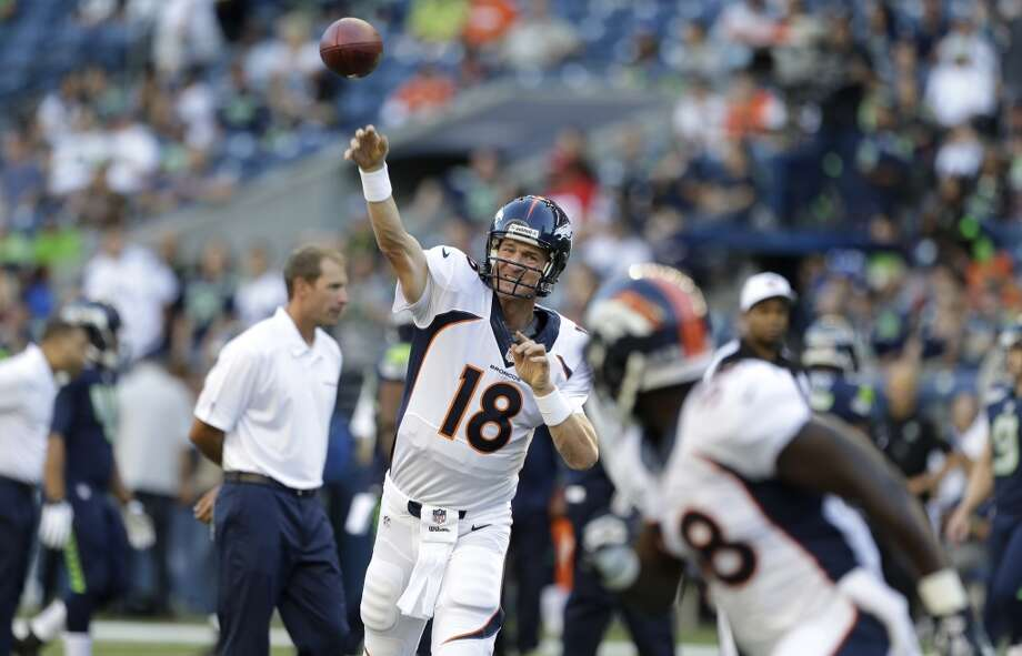 Denver Broncos quarterback Peyton Manning (18) passes to running back Montee Ball, right, as the Broncos warm up for a preseason NFL football game against the Seattle Seahawks, Saturday, Aug. 17, 2013, in Seattle. (AP Photo/Elaine Thompson) Photo: AP