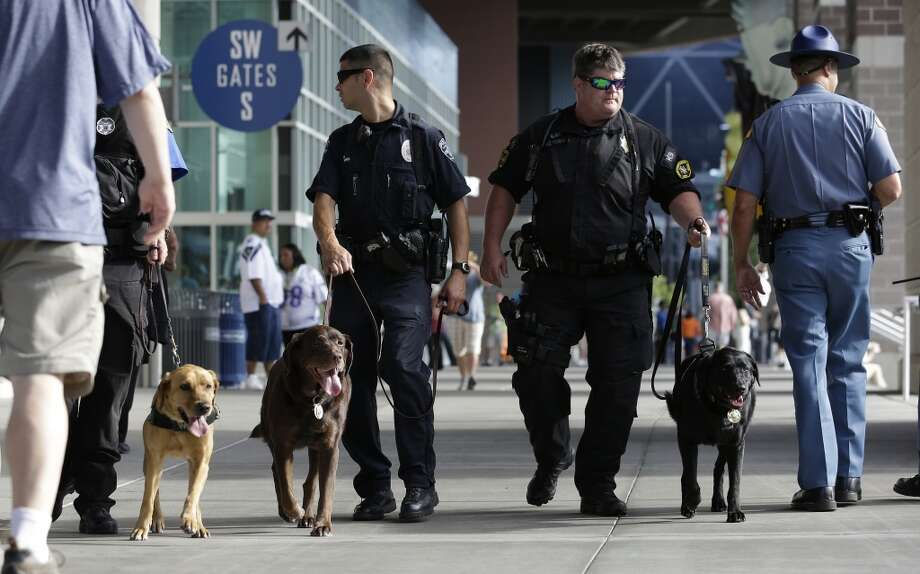 Pierce County Sheriff's Deputy Bill Hultman, second from right, walks with his dog Yoshi as he and other law enforcement officials patrol outside CenturyLink Field before a preseason NFL football game between the Seattle Seahawks and the Denver Broncos, Saturday, Aug. 17, 2013, in Seattle. (AP Photo/Elaine Thompson) Photo: AP