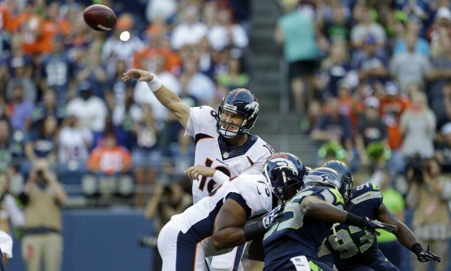 Denver Broncos quarterback Peyton Manning passes in the first half of a preseason NFL football game against the Seattle Seahawks, Saturday, Aug. 17, 2013, in Seattle. (AP Photo/Elaine Thompson) Photo: AP