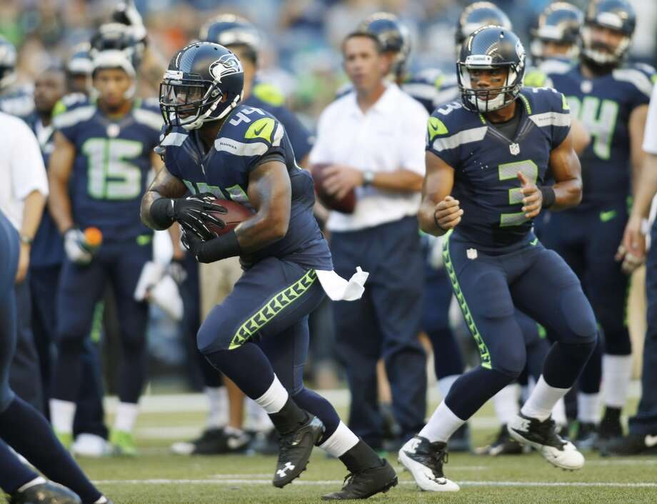 Seattle Seahawks running back Spencer Ware runs the ball after a handoff from Seahawks quarterback Russell Wilson (3) during warm-ups prior to a preseason NFL football game against the Denver Broncos, Saturday, Aug. 17, 2013, in Seattle. (AP Photo/John Froschauer) Photo: AP