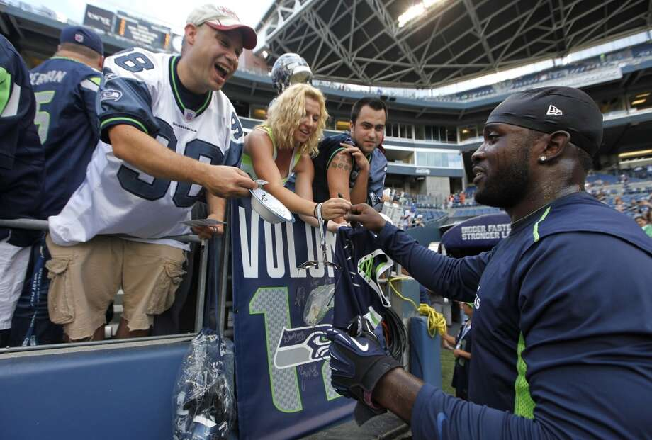 Seattle Seahawks' Kam Chancellor, right, signs autographs for fans prior to a preseason NFL football game against the Denver Broncos, Saturday, Aug. 17, 2013, in Seattle. (AP Photo/John Froschauer) Photo: AP