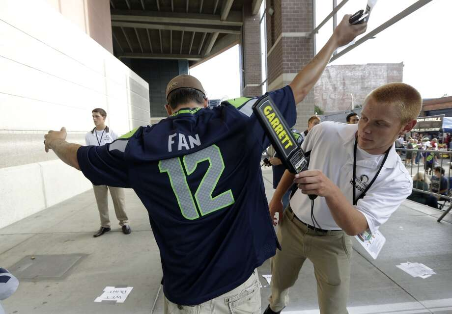 A security screener at CenturyLink Field checks a fan with a detector outside the stadium, at a preseason NFL football game between the Seattle Seahawks and the Denver Broncos, Saturday, Aug. 17, 2013, in Seattle. (AP Photo/Elaine Thompson) Photo: AP
