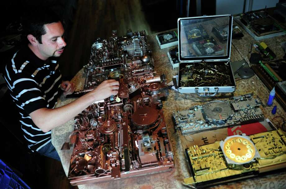 Michael Johnston, of Bridgeport, works on one of his unique clock sculptures. He uses found objects and  disassembled electronics to create his functional, futuristic art. Photo: Autumn Driscoll / Connecticut Post