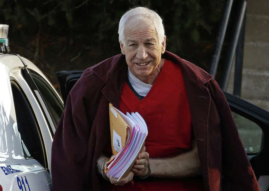 FILE - In this Jan. 10, 2013, file photo, former Penn State assistant football coach Jerry Sandusky arrives at the Centre County Courthouse for a post-sentencing hearing in Bellefonte, Pa. A lawyer says his client is the first to settle a civil claim against Penn State related to the Sandusky child sexual abuse case. Attorney Tom Kline confirmed in an email that the client known as Victim 5 when he testified at Sandusky's criminal trial has agreed to terms with the university. (AP Photo/Gene J. Puskar, File) Photo: Gene J. Puskar, STF / AP