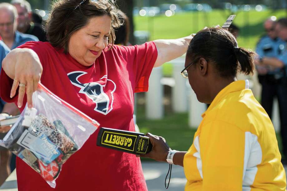 Houston Texans fan Regina Brower holds her belongings in a clear bag Saturday as he goes through security screening before entering Reliant Stadium to watch a preseason game against the Miami Dolphins. Photo: Smiley N. Pool, Staff / © 2013  Houston Chronicle