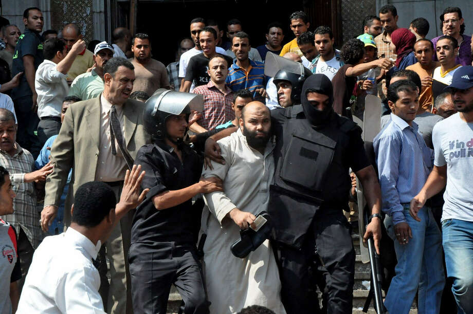 Egyptian security forces escort an Islamist supporter of the Muslim Brotherhood from the al-Fath mosque in Cairo after hundreds of protesters barricaded themselves inside overnight. Photo: Hussein Tallal / Associated Press