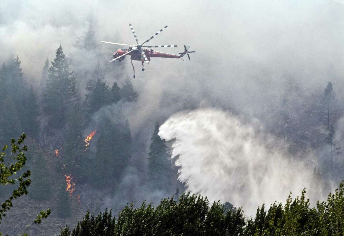 A firefighting helicopter drops water on the Beaver Creek Fire in central Idaho. The fire started Aug. 7 and has grown significantly in the past few days, burning through tinder-dry brush and timber.