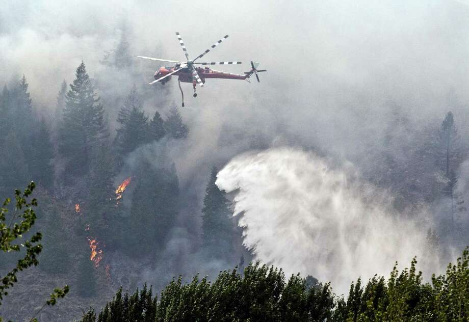 A firefighting helicopter drops water on the Beaver Creek Fire in central Idaho. The fire started Aug. 7 and has grown significantly in the past few days, burning through tinder-dry brush and timber. Photo: Darin Oswald / Idaho Statesman