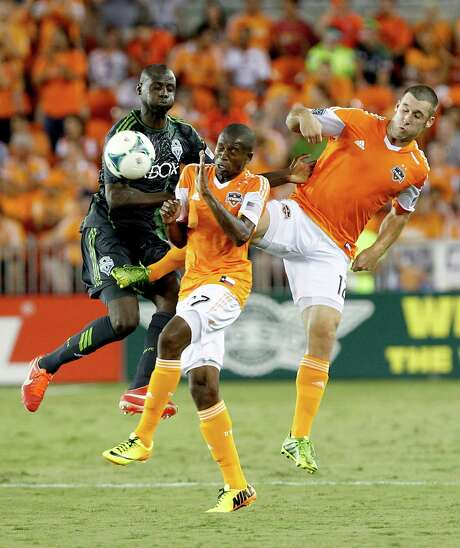 Sounders defender Djimi Trure, left, finds himself squeezed out by the Dynamo's Boniek Garcia, center, and Will Bruin in the first half Saturday night. Photo: Thomas B. Shea / © 2013 Thomas B. Shea