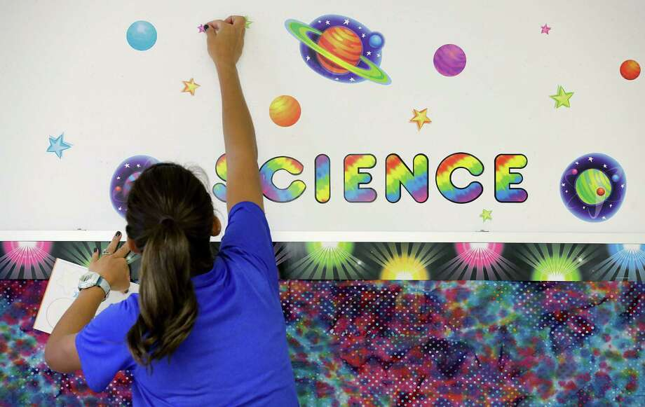 Courtney Williams, a fourth grade teacher at Somerset Elementary School, puts up decorations in her classroom preparing for the first day of school. Photo: Bob Owen / San Antonio Express-News