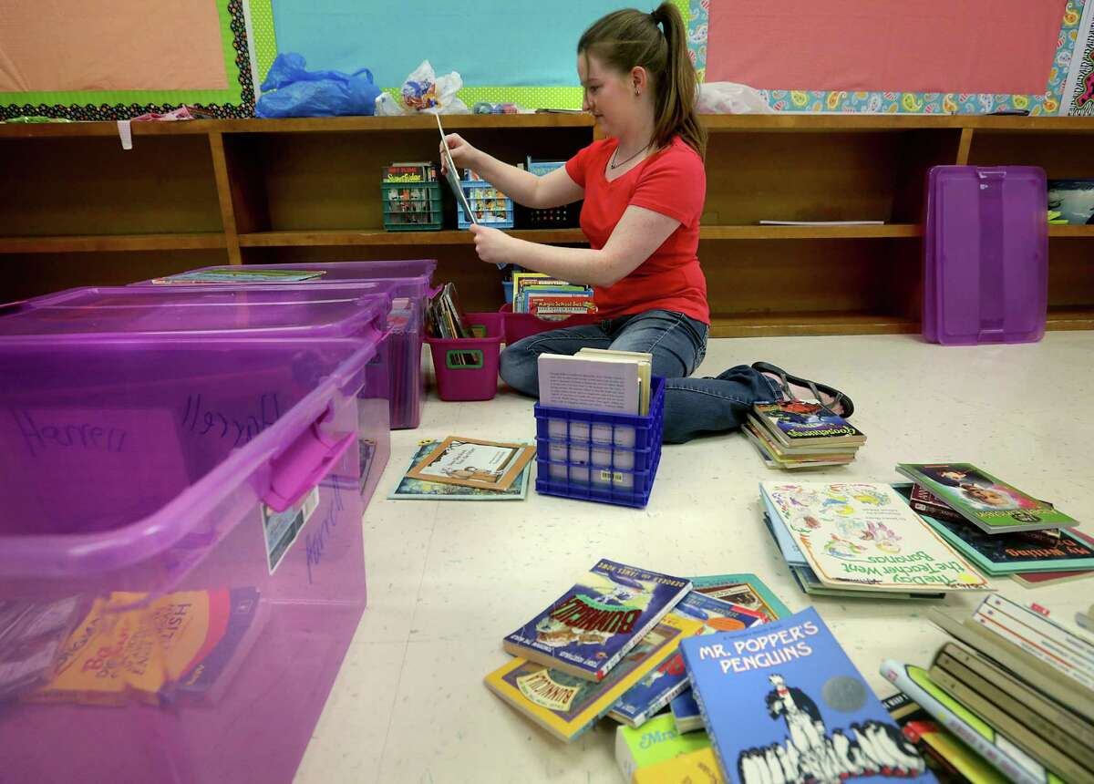 LaRee Harrell, (cq) a second year teacher at Somerset Elementary School teaching 4th grade this year, looks through books as she sets up her in-classroom library. Somerset ISD has implemented a revolutionary new teacher pay system based on their performance including test scores and classroom observations. Friday, August 16, 2013.
