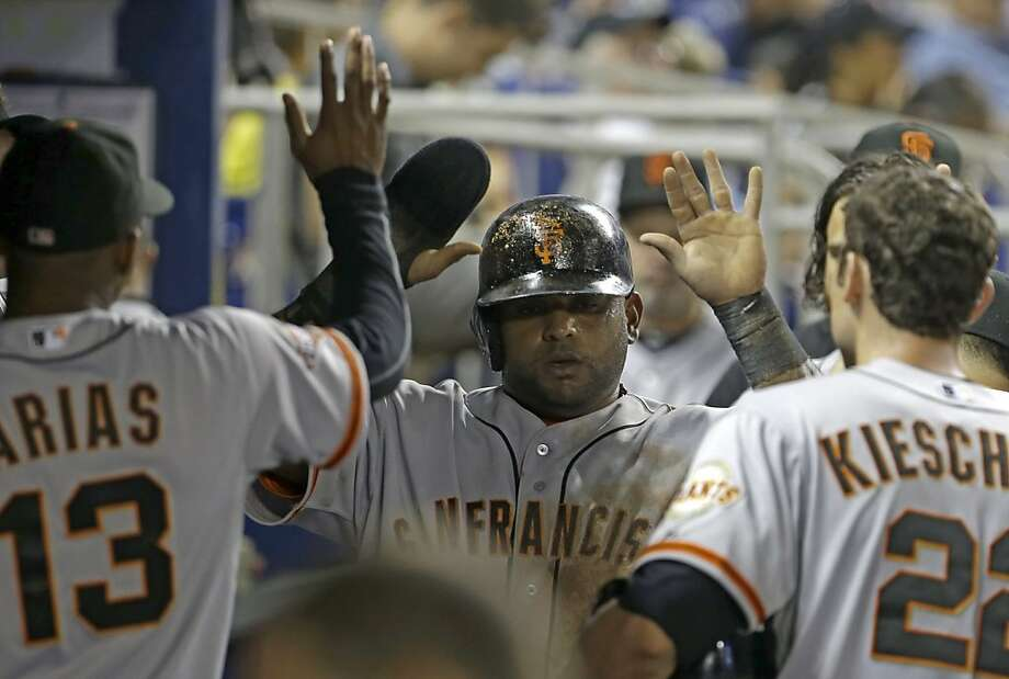 Pablo Sandoval (center), who reached on an infield single in the fourth, celebrates after scoring on Gregor Blanco's triple. Photo: Alan Diaz, Associated Press
