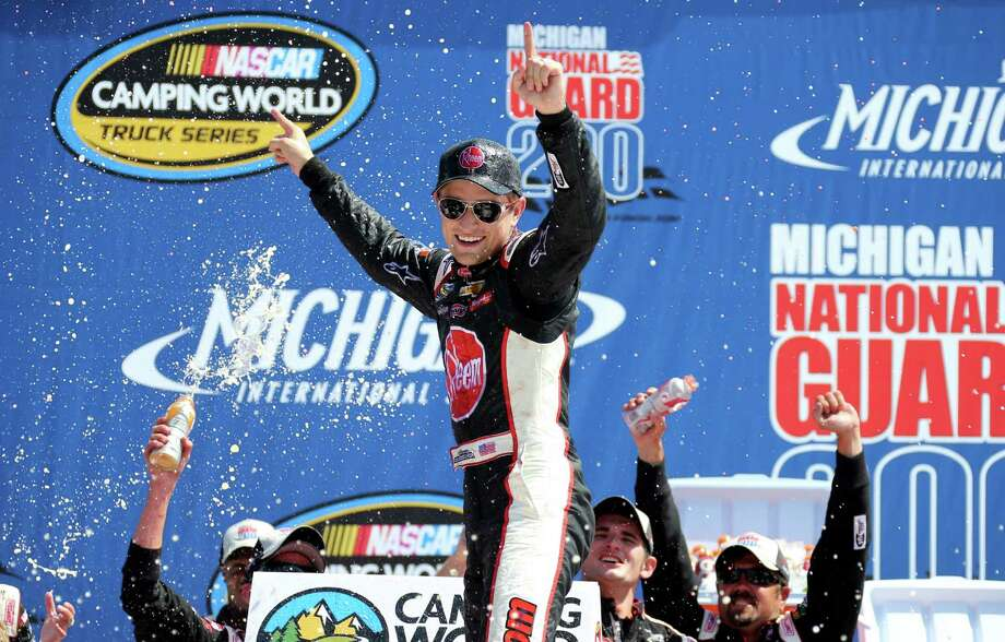 James Buescher celebrates winning the NASCAR Camping World Truck series Michigan National Guard 200 auto race at Michigan International Speedway in Brooklyn, Mich., Saturday, Aug. 17, 2013. (AP Photo/Bob Brodbeck)   ORG XMIT: MIPS114 Photo: Bob Brodbeck / FR3471 AP