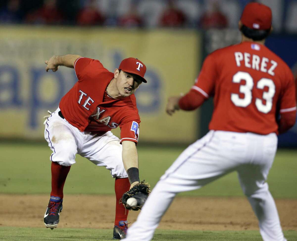 Rangers second baseman Ian Kinsler stretches to catch a pop up by Michael Morse as pitcher Martin Perez watches.