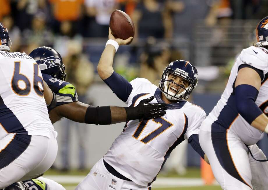 Denver Broncos quarterback Brock Osweiler (17) is knocked down by Seattle Seahawks' Brandon Mebane while passing in the first half of a preseason NFL football game, Saturday, Aug. 17, 2013, in Seattle. (AP Photo/Elaine Thompson) Photo: AP