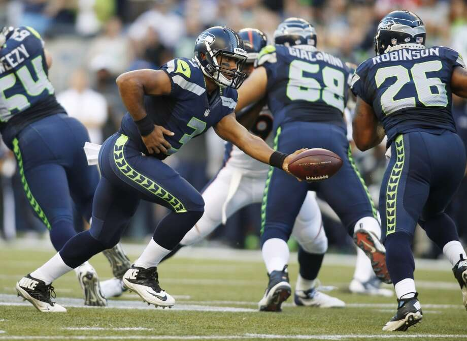 Seattle Seahawks quarterback Russell Wilson (3) hands off to Michael Robinson (26) in the first half of a preseason NFL football game against the Denver Broncos, Saturday, Aug. 17, 2013, in Seattle. (AP Photo/John Froschauer) Photo: AP