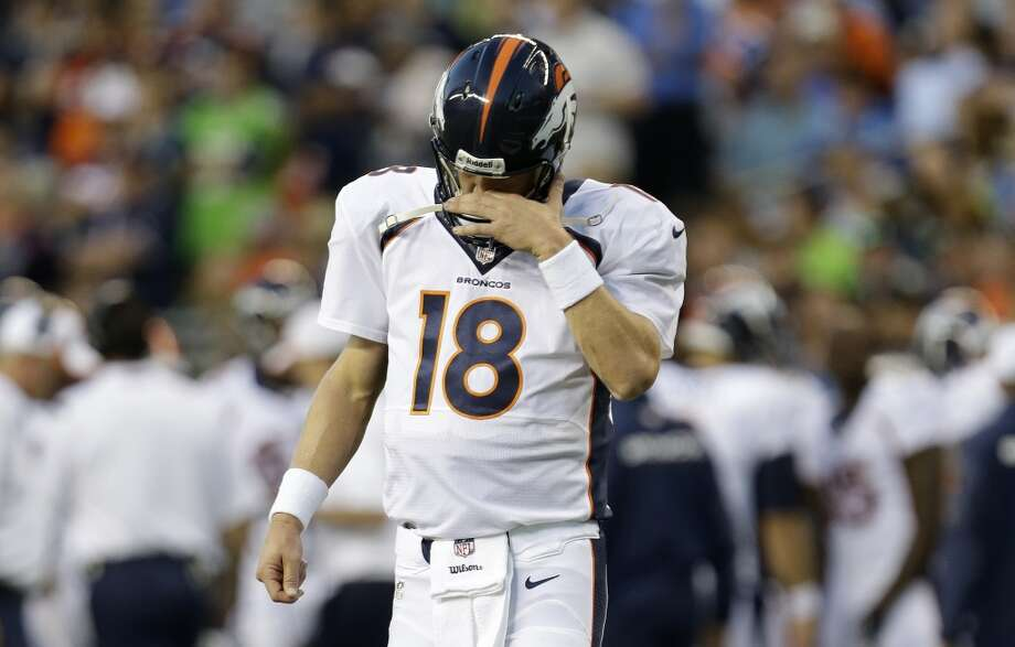 Denver Broncos quarterback Peyton Manning walks on the field after a play  in the first half of a preseason NFL football game against the Seattle Seahawks, Saturday, Aug. 17, 2013, in Seattle. (AP Photo/Elaine Thompson) Photo: AP
