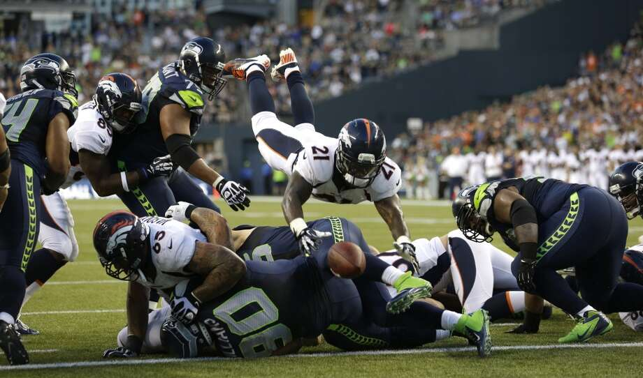Denver Broncos Denver Broncos running back Ronnie Hillman (21) fumbles as he goes over the top on a play against the Seattle Seahawks in the first half of a preseason NFL football game, Saturday, Aug. 17, 2013, in Seattle. The fumble was picked up by Seahawks' Brandon Browner (not shown) and returned for a touchdown. (AP Photo/Elaine Thompson) Photo: AP