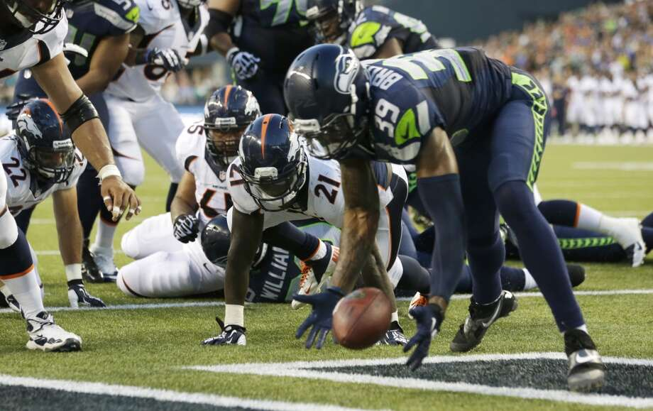 Denver Broncos running back Ronnie Hillman (21) watches as Seattle Seahawks cornerback Brandon Browner (39) picks up Hillman's fumble in the first half of a preseason NFL football game, Saturday, Aug. 17, 2013, in Seattle. Browner returned the fumble for a touchdown. (AP Photo/Elaine Thompson) Photo: AP