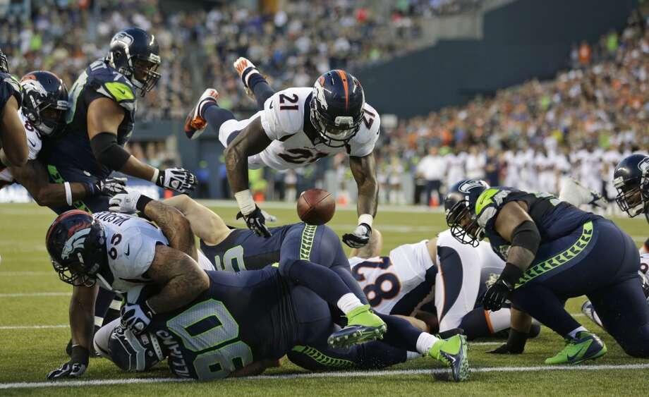 Denver Broncos running back Ronnie Hillman (21) fumbles as he goes over the top on a play against the Seattle Seahawks in the first half of a preseason NFL football game, Saturday, Aug. 17, 2013, in Seattle. The fumble was picked up by Seahawks' Brandon Browner, not seen, and returned for a touchdown. (AP Photo/Elaine Thompson) Photo: AP
