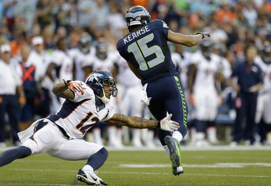 Seattle Seahawks' Jermaine Kearse (15) dodges Denver Broncos' Andre Caldwell (12) and runs for a 107-yard touchdown on a kickoff return in the first half of a preseason NFL football game, Saturday, Aug. 17, 2013, in Seattle. (AP Photo/Elaine Thompson) Photo: AP