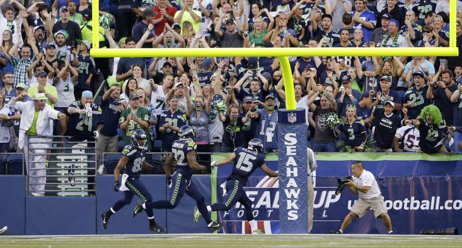 Seattle Seahawks fans cheer after Seahawks' Jermaine Kearse (15) scored a touchdown on a 107-yard kickoff return against the Denver Broncos in the first half of a preseason NFL football game, Saturday, Aug. 17, 2013, in Seattle. Running with Kearse are Seahawks' Doug Baldwin (89) and Jeron Johnson (32). (AP Photo/Elaine Thompson) Photo: AP