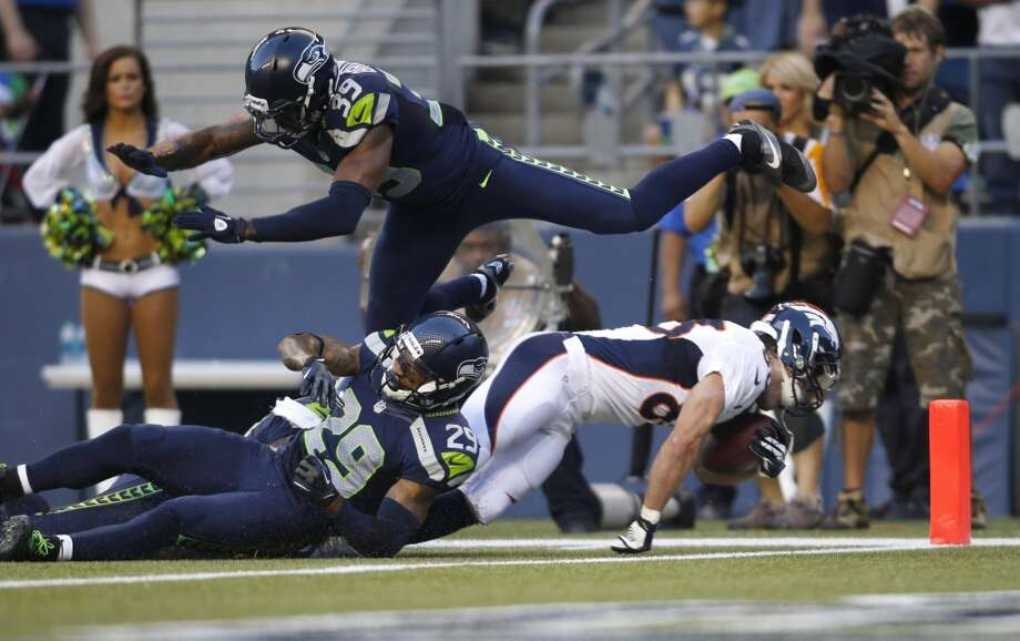 Denver Broncos wide receiver Wes Welker, lower right, scores a touchdown under the defense of a leaping Seattle Seahawks cornerback Brandon Browner (39) and a tackle attempt by Seahawks' Earl Thomas (29) in the first half of a preseason NFL football game, Saturday, Aug. 17, 2013, in Seattle.  (AP Photo/John Froschauer) Photo: AP