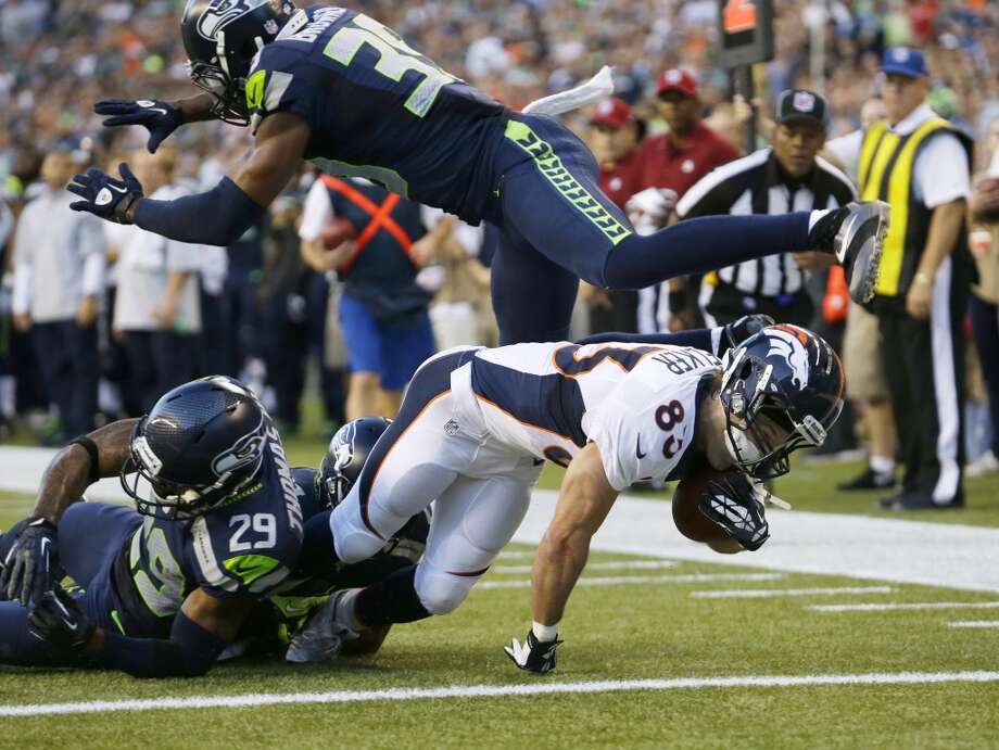 Denver Broncos wide receiver Wes Welker scores a touchdown under the defense of a leaping Seattle Seahawks cornerback Brandon Browner (39) and tackles by Seahawks' Earl Thomas (29) and Antoine Winfield (obscured) in the first half of a preseason NFL football game, Saturday, Aug. 17, 2013, in Seattle. (AP Photo/Elaine Thompson) Photo: ASSOCIATED PRESS