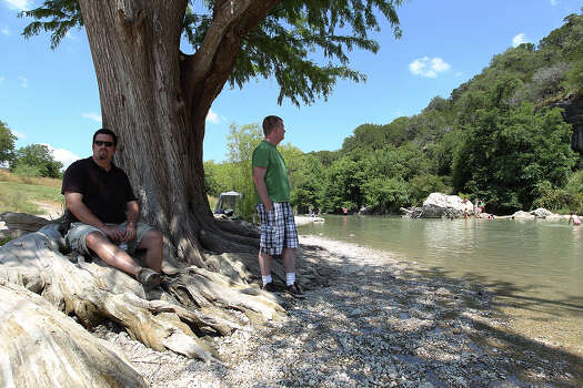 Marty Robinson (left) of Houston and his friend Ryan Flynn from Fort Collins, Colorado take shade under a Cypress tree at Guadalupe River State Park on Saturday, Aug. 17, 2013. When water levels are sufficient, both men would be in nearly waist-high water. Drought conditions have lowered attendance to the park as well as other area water attractions like the Bergheim Campground. Because of the low flow and lack of water on the river, Bergheim Campground has halted renting inner tubes, canoes and kayaks for the time being. Photo: Kin Man Hui, San Antonio Express-News / ©2013 San Antonio Express-News