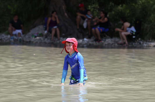Andrew Robinson, 6, from Houston wades across a section of the river at Guadalupe River State Park on Saturday, Aug. 17, 2013. The shortage of water has had an effect on attendance since the park is forced to shut off water supplies and bathroom facilities to guests. Over the weekend, some of the camp sites do have running water lines but the bathrooms are still closed with only portable toilets available. The conditions have lowered attendance to the park as well as other area water attractions like the Bergheim Campground. Because of the low flow and lack of water on the river, Bergheim Campground has halted renting inner tubes, canoes and kayaks for the time being. Photo: Kin Man Hui, San Antonio Express-News / ©2013 San Antonio Express-News