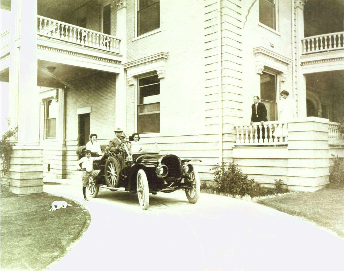 David Woodward steers of one of the city's first autos in this circa 1906 photo of his home, now the Woman's Club headquarters.