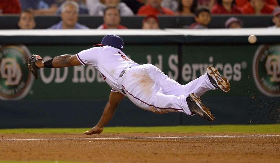 Angels third baseman Chris Nelson can't reach a ball hit for a single by Chris Carter. Photo: Mark J. Terrill, Associated Press
