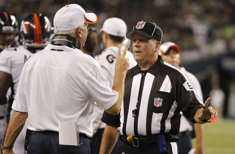 Denver Broncos head coach John Fox, left, discusses a play with an official in the second half of a preseason NFL football game against the Seattle Seahawks, Saturday, Aug. 17, 2013, in Seattle. (AP Photo/John Froschauer) Photo: AP