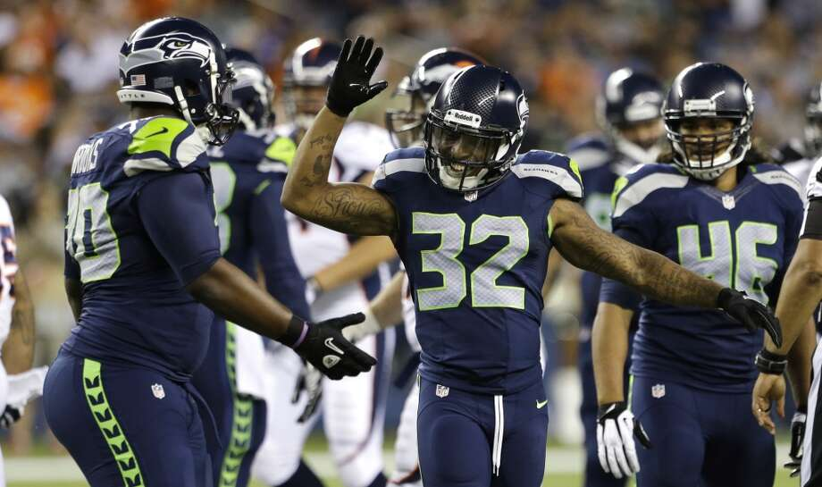 Seattle Seahawks' Jeron Johnson (32) and Michael Brooks, left, celebrate a play against the Denver Broncos in the second half of a preseason NFL football game, Saturday, Aug. 17, 2013, in Seattle. (AP Photo/Elaine Thompson) Photo: AP