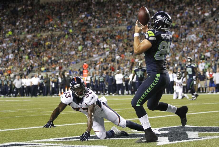 Seattle Seahawks tight end Sean McGrath (84) bobbles a pass before pulling it down for a touchdown as Denver Broncos' Duke Ihenacho (33) looks on in the first half of a preseason NFL football game, Saturday, Aug. 17, 2013, in Seattle. (AP Photo/John Froschauer) Photo: AP