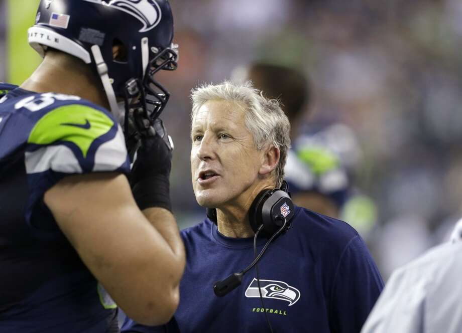 Seattle Seahawks head coach Pete Carroll, right, talks with Breno Giacomini on the sidelines against the Denver Broncos in the first half of a preseason NFL football game, Saturday, Aug. 17, 2013, in Seattle. (AP Photo/Elaine Thompson) Photo: AP