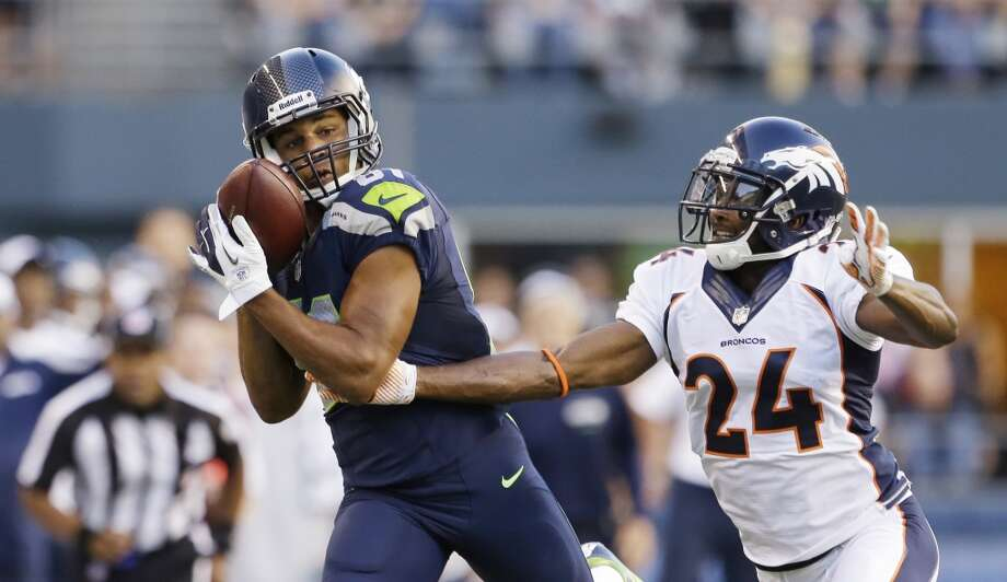 Seattle Seahawks' Golden Tate, left, cradles the ball as he pulls in a long reception as Denver Broncos' Champ Bailey defends in the first half of a preseason NFL football game, Saturday, Aug. 17, 2013, in Seattle. (AP Photo/Elaine Thompson) Photo: ASSOCIATED PRESS