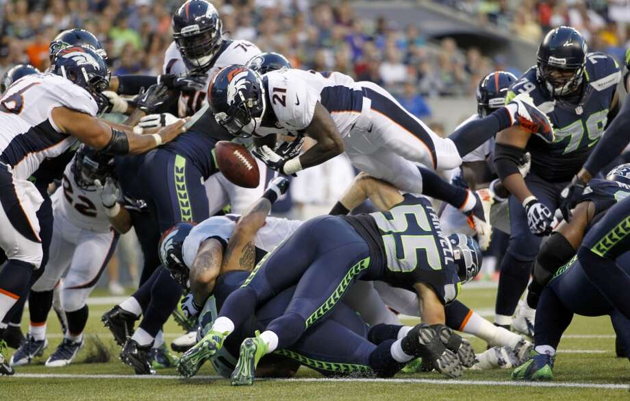 Denver Broncos running back Ronnie Hillman (21) fumbles as he goes over Seattle Seahawks' Heath Farwell (55) in the first half of a preseason NFL football game, Saturday, Aug. 17, 2013, in Seattle. The fumble was picked up by Seahawks' Brandon Browner (not shown) and returned for a touchdown.  (AP Photo/John Froschauer) Photo: ASSOCIATED PRESS