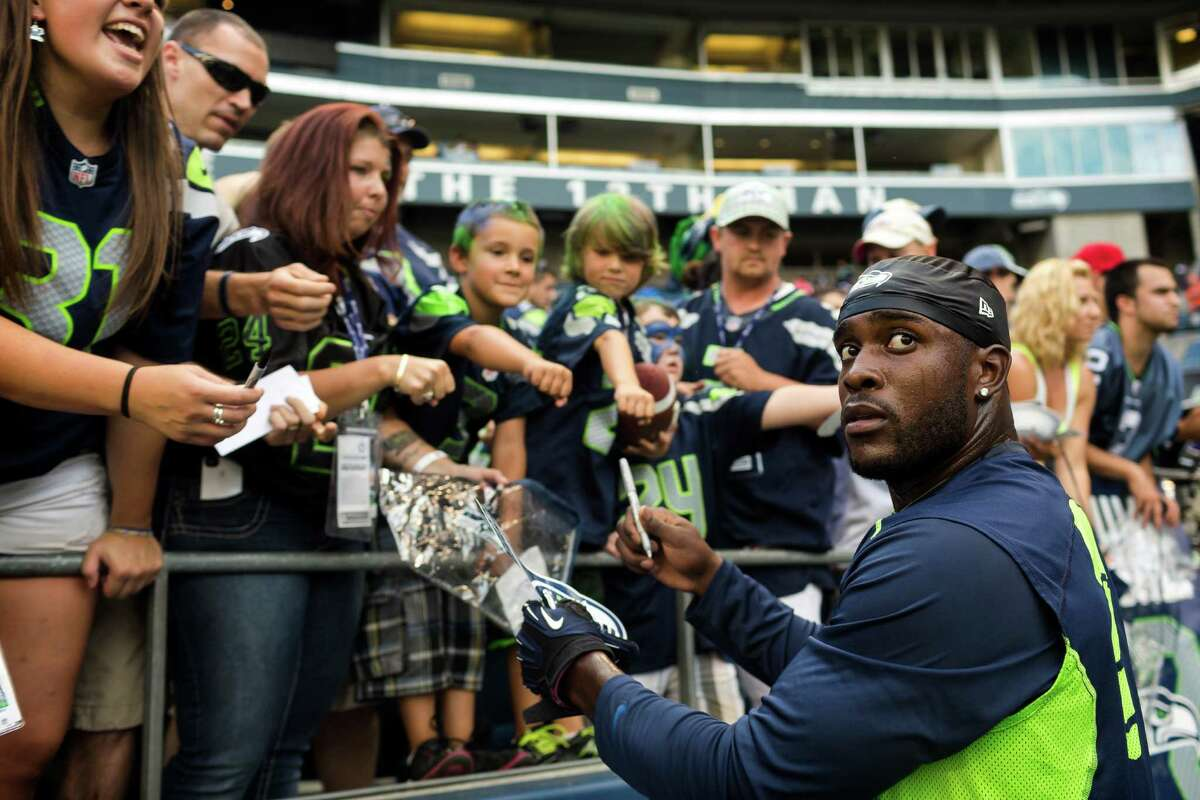 Players sign autographs for fans before the first half of a preseason game Saturday, August 17, 2013, at CenturyLink Field in Seattle. The event marked the Seahawks first home game this season.