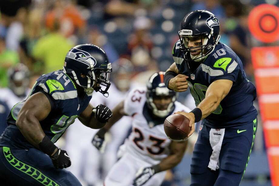 Seahawks quarterback Brady Quinn, right, hands off to Spencer Ware, left, during the second half of a preseason game Saturday, August 17, 2013, at CenturyLink Field in Seattle. The Seahawks beat the Broncos 40-10. The event marked the Seahawks first home game this season. Photo: JORDAN STEAD, SEATTLEPI.COM / SEATTLEPI.COM