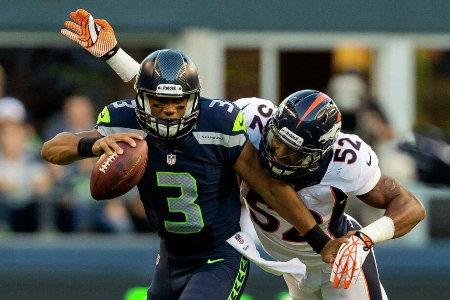 Quarterback Russell Wilson, left, gets sacked by Wesley Woodyard, right, during the first half of a preseason game Saturday, August 17, 2013, at CenturyLink Field in Seattle. The event marked the Seahawks first home game this season. Photo: JORDAN STEAD, SEATTLEPI.COM / SEATTLEPI.COM