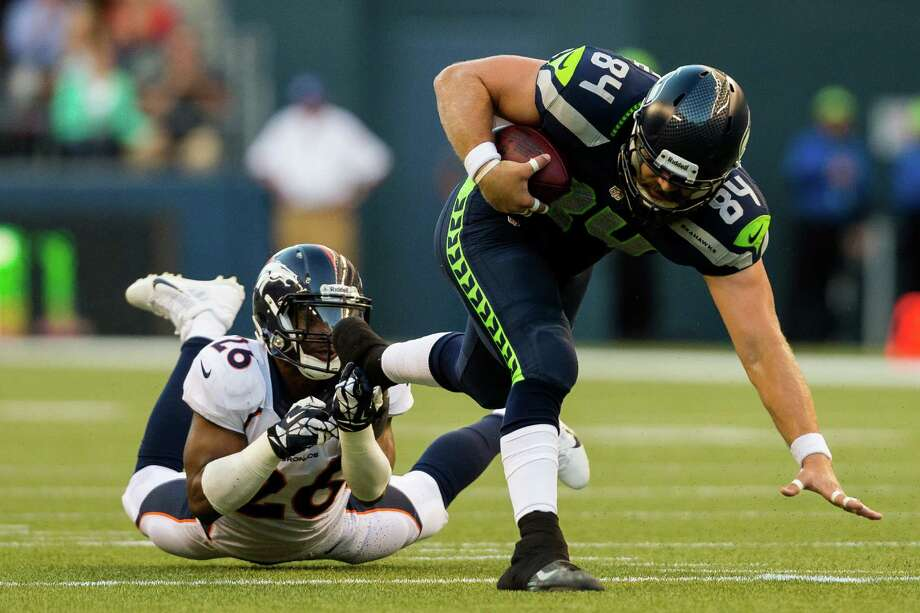 Sean McGrath, right, squeezes out of a grab by a Bronco during the first half of a preseason game Saturday, August 17, 2013, at CenturyLink Field in Seattle. The event marked the Seahawks first home game this season. Photo: JORDAN STEAD, SEATTLEPI.COM / SEATTLEPI.COM