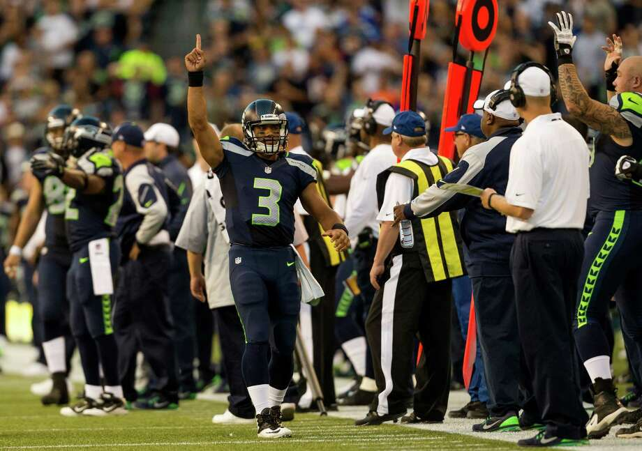 Russell Wilson, center, defiantly raises a hand following a touchdown by Jermaine Kearse during the first half of a preseason game Saturday, August 17, 2013, at CenturyLink Field in Seattle. The event marked the Seahawks first home game this season. Photo: JORDAN STEAD, SEATTLEPI.COM / SEATTLEPI.COM