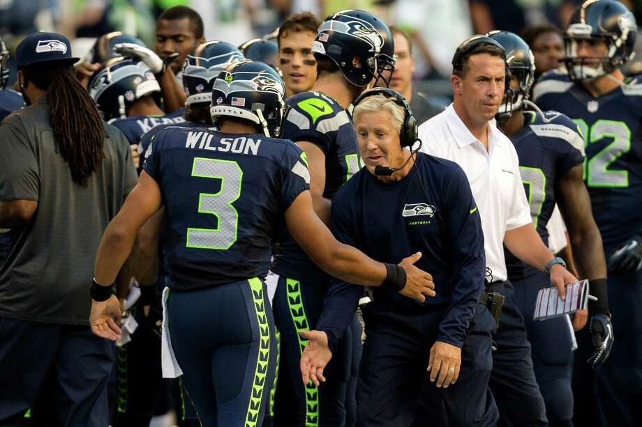 Head coach Pete Carroll, right, congratulates Russell Wilson, left, following a play during the first half of a preseason game Saturday, August 17, 2013, at CenturyLink Field in Seattle. The event marked the Seahawks first home game this season. Photo: JORDAN STEAD, SEATTLEPI.COM / SEATTLEPI.COM