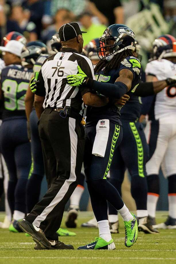 Richard Sherman, right, messes around with a ref during the first half of a preseason game Saturday, August 17, 2013, at CenturyLink Field in Seattle. The event marked the Seahawks first home game this season. Photo: JORDAN STEAD, SEATTLEPI.COM / SEATTLEPI.COM