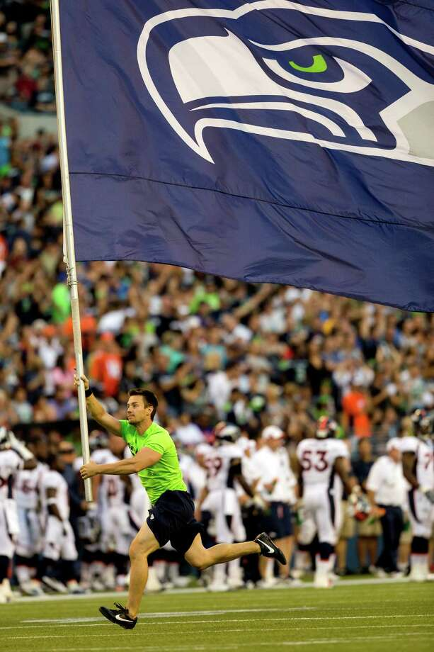 A runner carries a Seahawks flag following a touchdown for the home team during the first half of a preseason game Saturday, August 17, 2013, at CenturyLink Field in Seattle. The event marked the Seahawks first home game this season. Photo: JORDAN STEAD, SEATTLEPI.COM / SEATTLEPI.COM