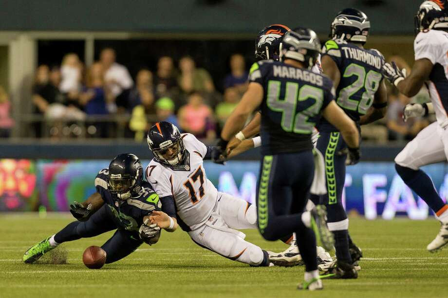 Seahawks player O'Brien Schofield, left, and Denver Bronco's player Brock Osweiler, center, left, slip and fall while both pursuing a ball during the first half of a preseason game Saturday, August 17, 2013, at CenturyLink Field in Seattle. The event marked the Seahawks first home game this season. Photo: JORDAN STEAD, SEATTLEPI.COM / SEATTLEPI.COM