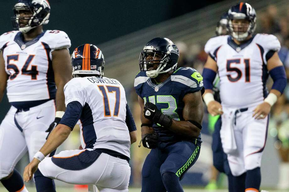 Kyle Knox, center right, screams after tackling a Denver Bronco quarterback during the second half of a preseason game Saturday, August 17, 2013, at CenturyLink Field in Seattle. The Seahawks beat the Broncos 40-10. The event marked the Seahawks first home game this season. Photo: JORDAN STEAD, SEATTLEPI.COM / SEATTLEPI.COM