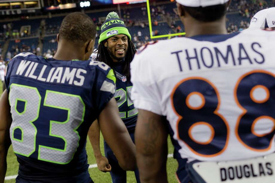 Richard Sherman chats with teammates and Denver Broncos players following the second half of a preseason game Saturday, August 17, 2013, at CenturyLink Field in Seattle. The Seahawks beat the Broncos 40-10. The event marked the Seahawks first home game this season. Photo: JORDAN STEAD, SEATTLEPI.COM / SEATTLEPI.COM